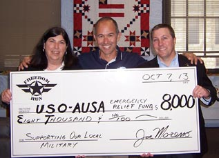 photo of a check being presented to USO and AUSA